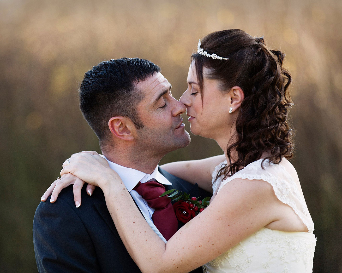 Groom cradling bride and kissing one another with brown shimmering background of sun setting on fields