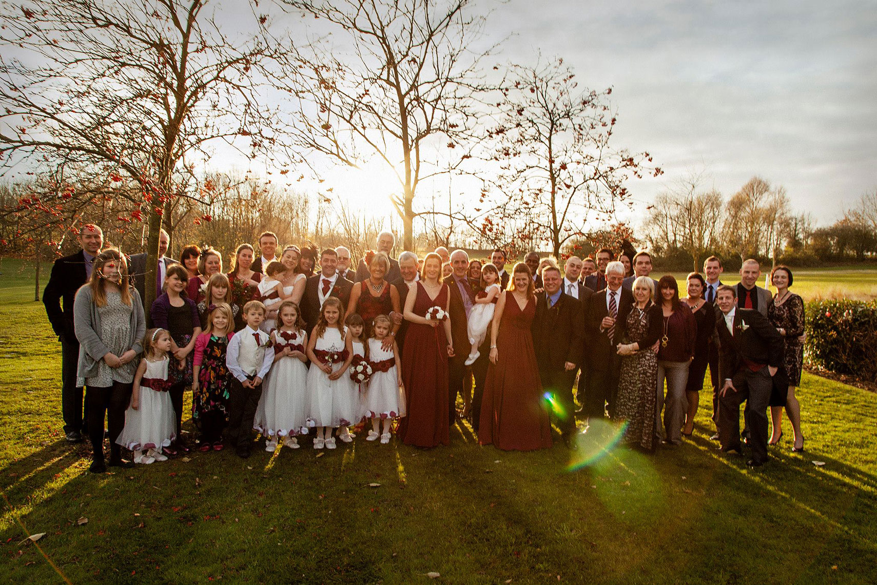Sun setting behind wedding party taking place in green fields with trees