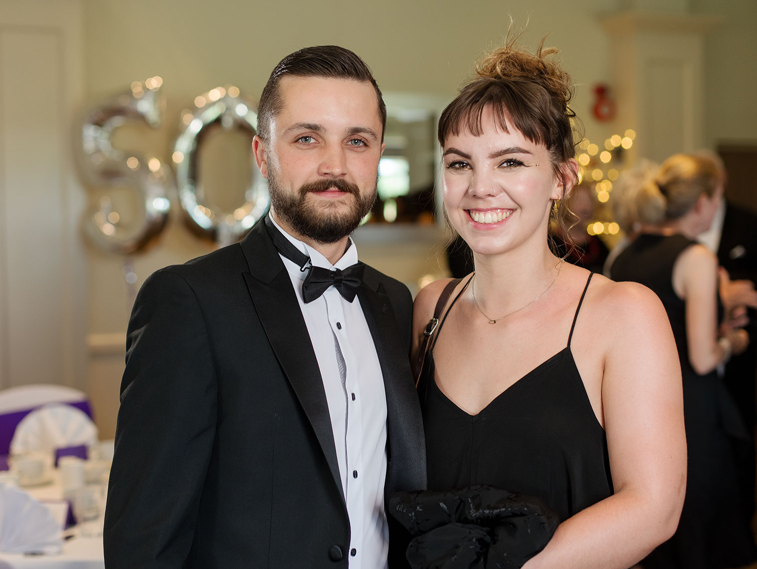 Man with beard and dark suit posing with smiling young lady in formal dress