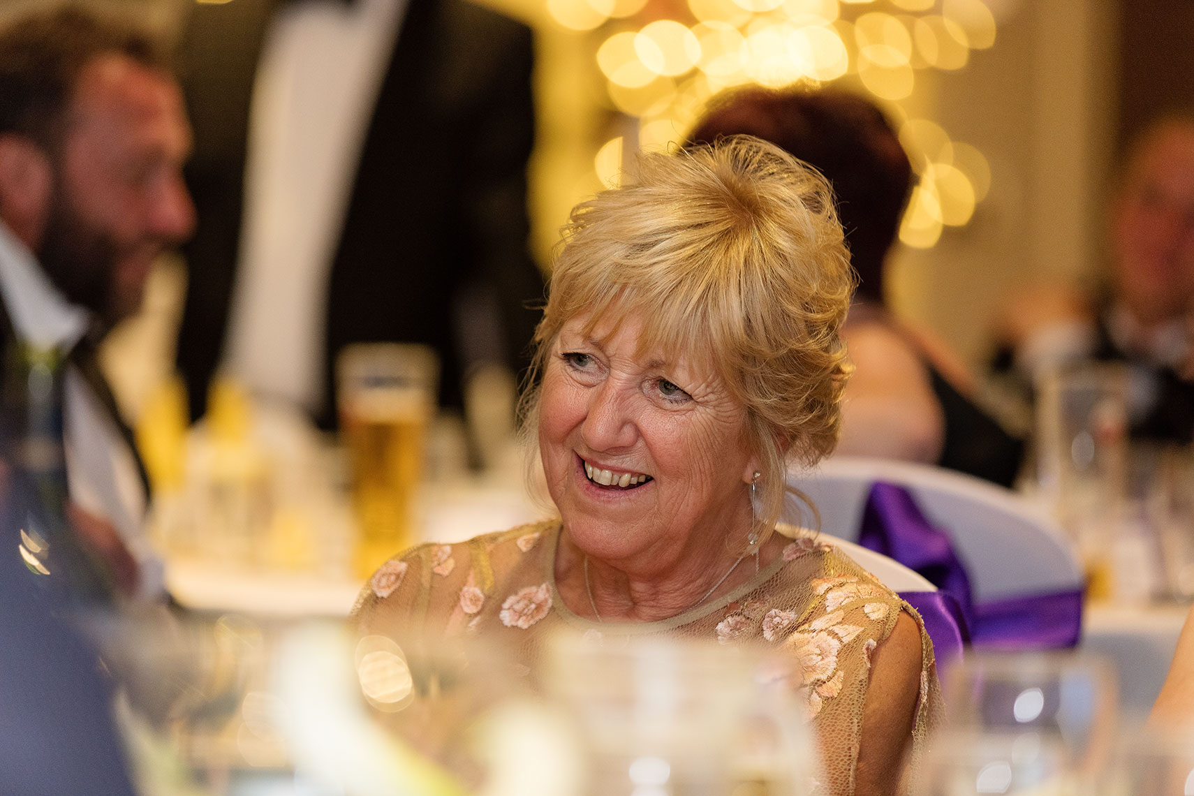 Smiling older lady wearing ornate  golden gown watching speaker at birthday reception