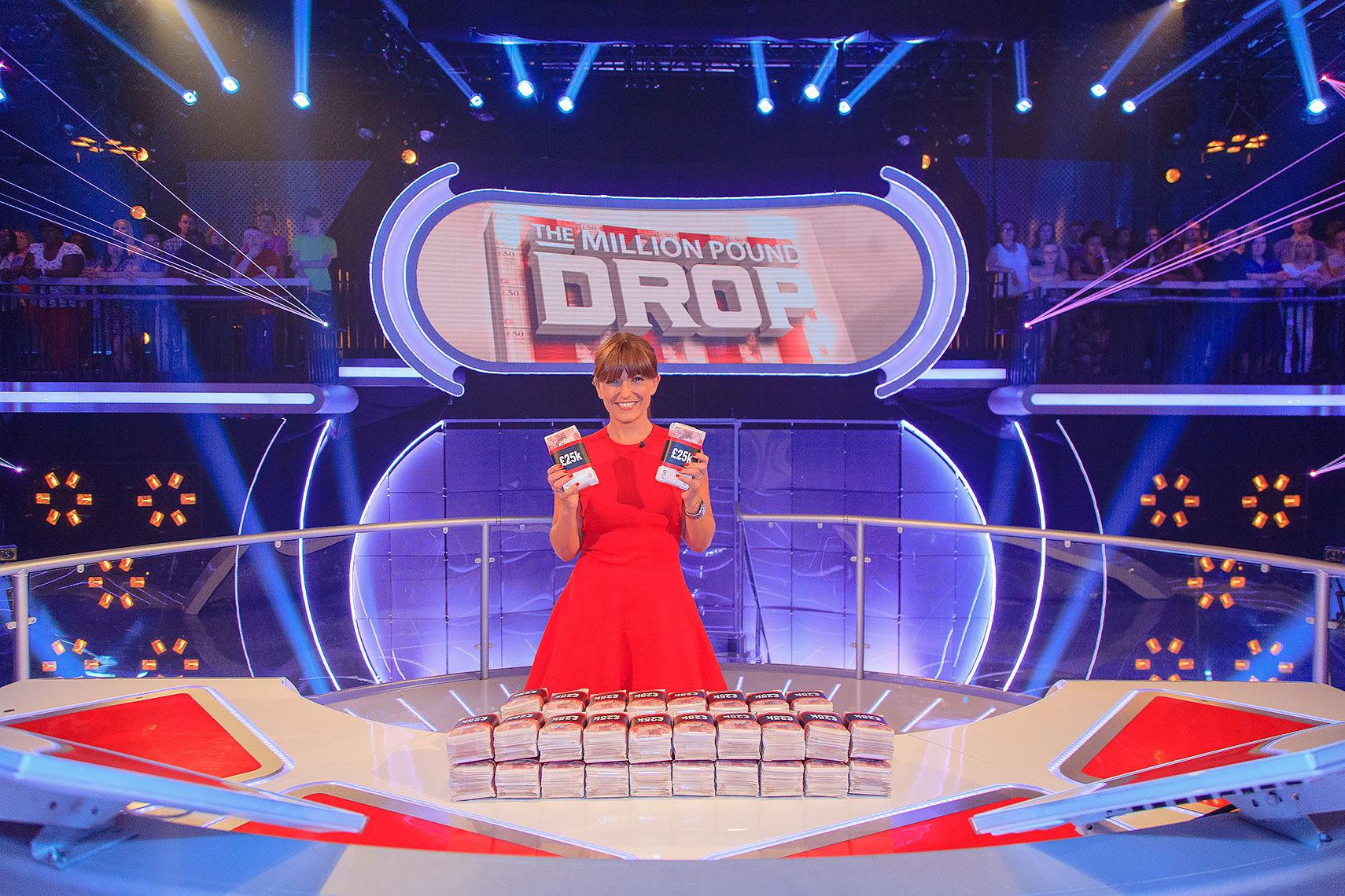 Television celebrity Davina McCall wearing gorgeous red dress and displaying cash on television set