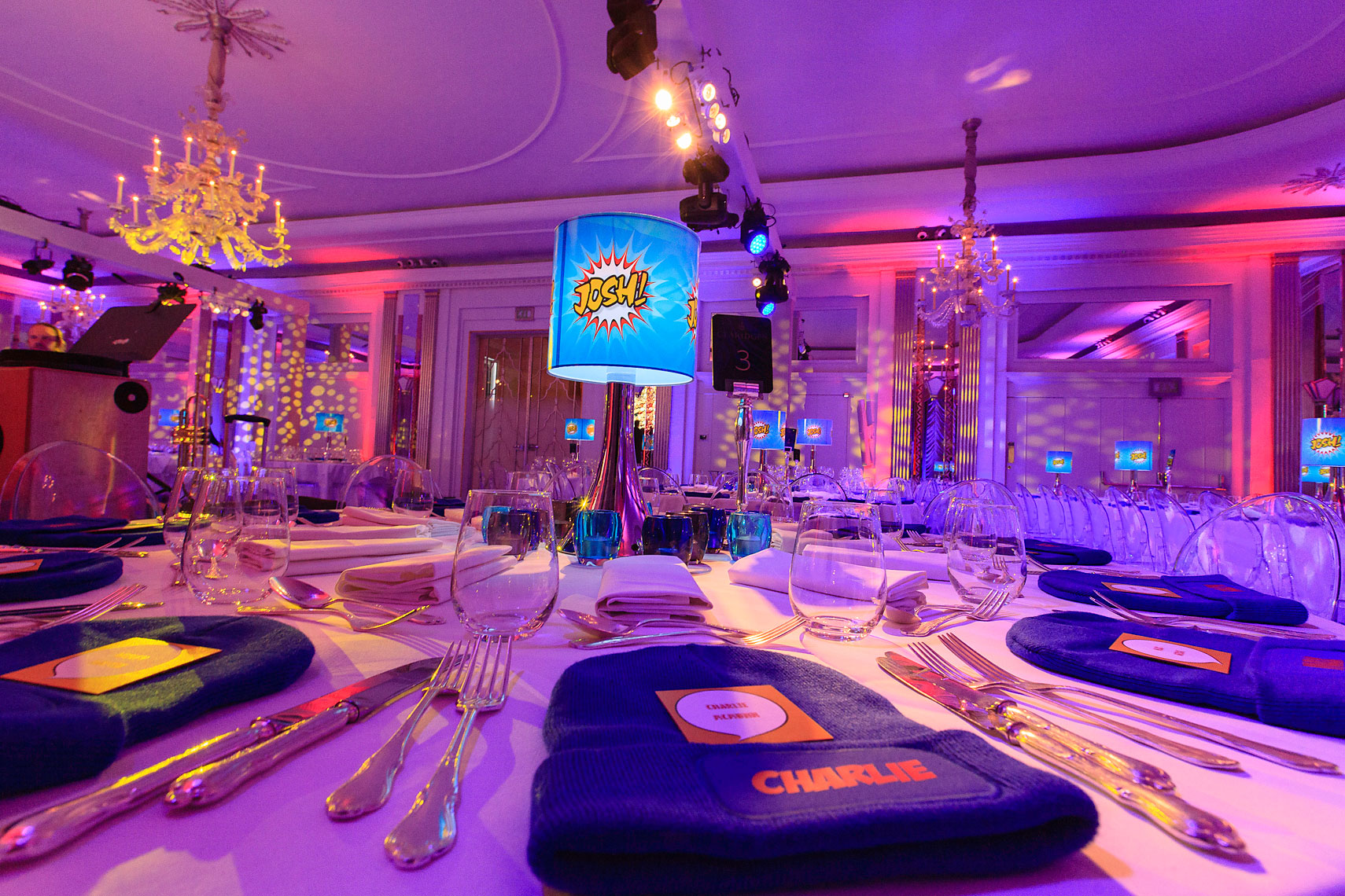 Corporate hotel ballroom interior decorated with floral bouquets on tables featuring purple lighting