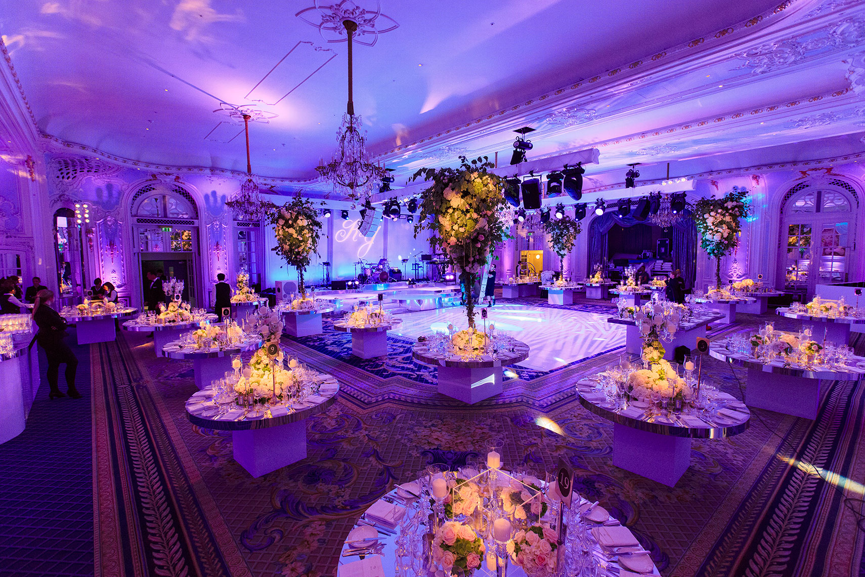 Corporate event space decorated with floral bouquets on tables featuring purple and black lighting interior