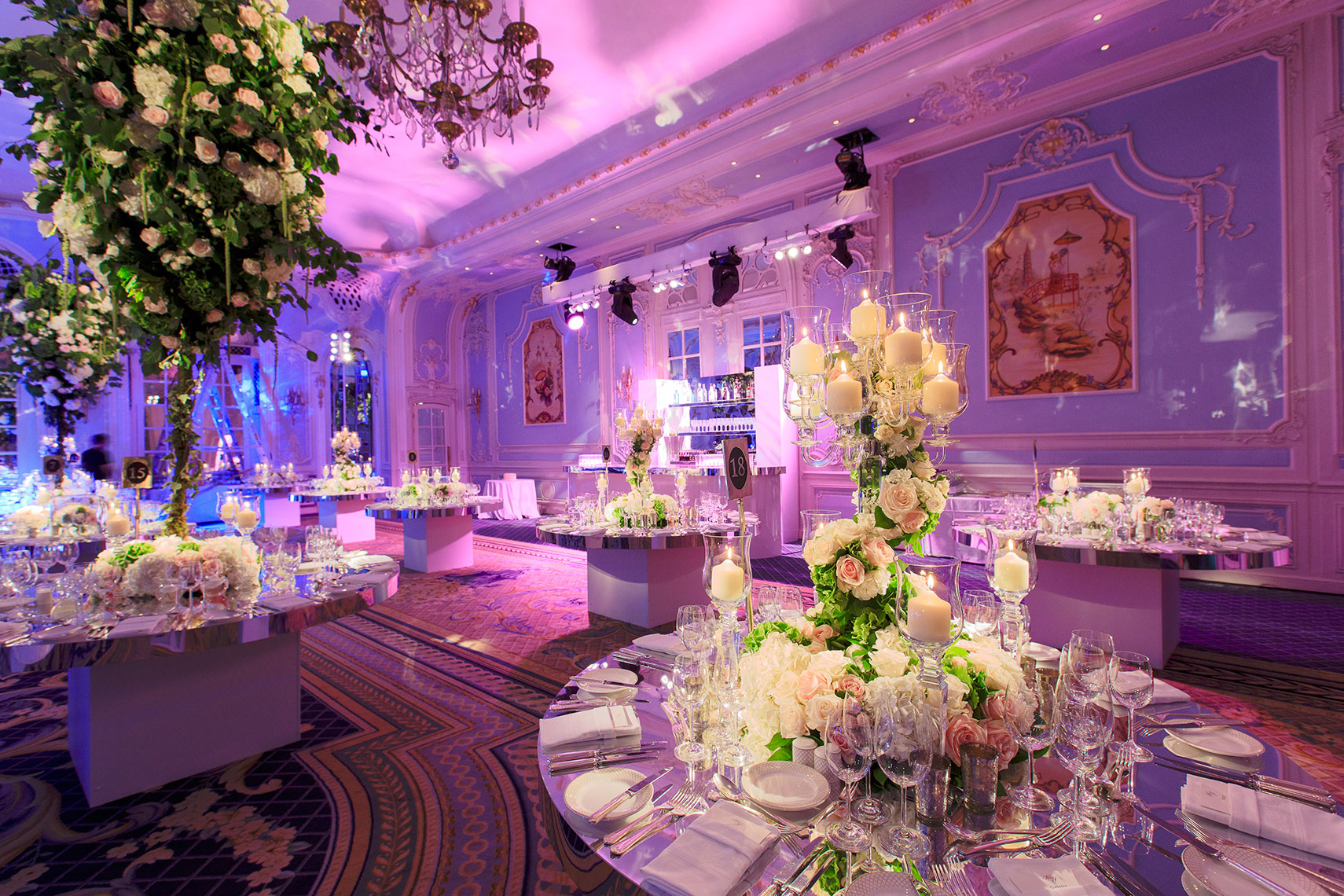 Ornate corporate event space decorated with large floral bouquets on tables with pink lighting