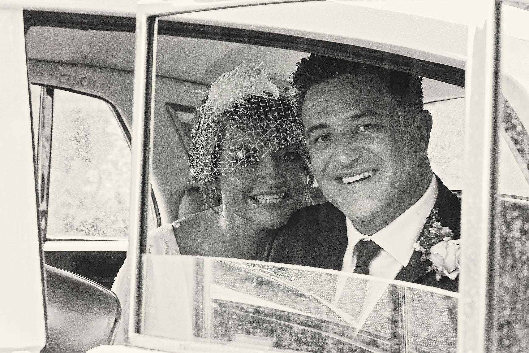 Beautiful smiling bride sitting next to happy groom in wedding car