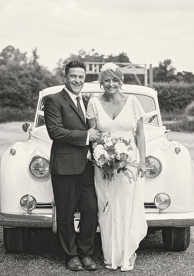 Smiling bride and groom posing in front of vintage car