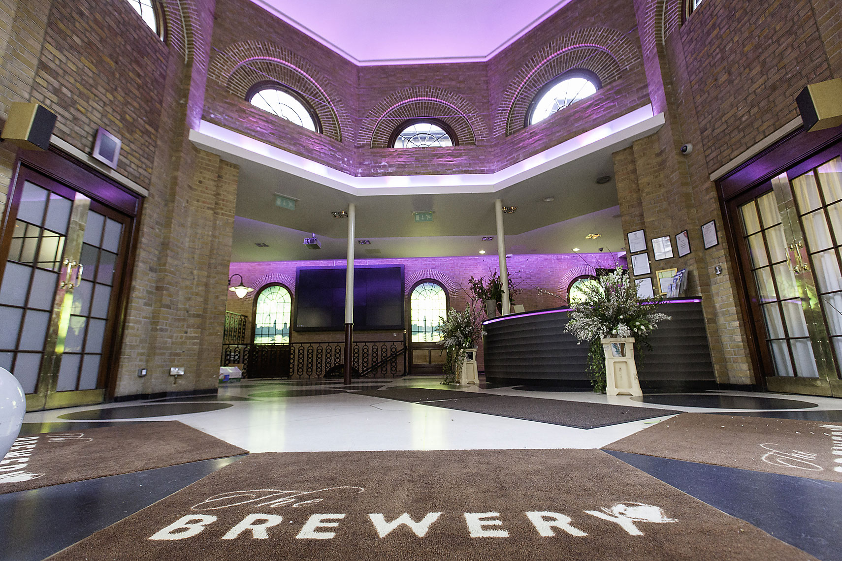 Interior entrance of high-end hotel, with high ceilings and purple decorative lighting
