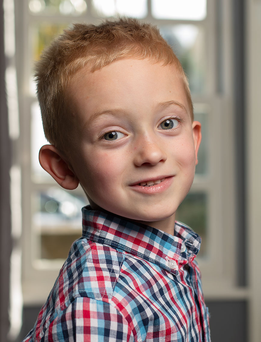 Smiling young boy with blonde hair and head turned looking into camera