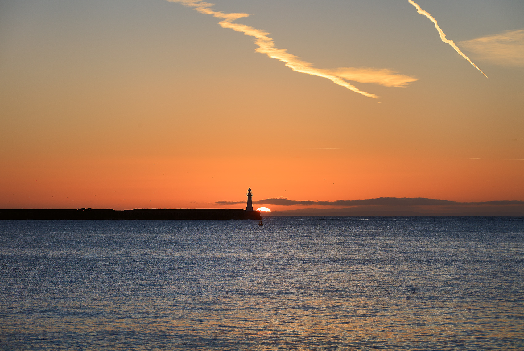 Sun rising over the sea with lighthouse in the distance of Dover, Kent UK