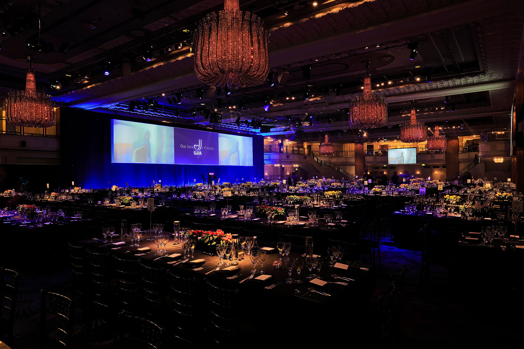 Interior event ballroom space with tables set up for evening event, decorated with floral bouquets and dramatic lighting