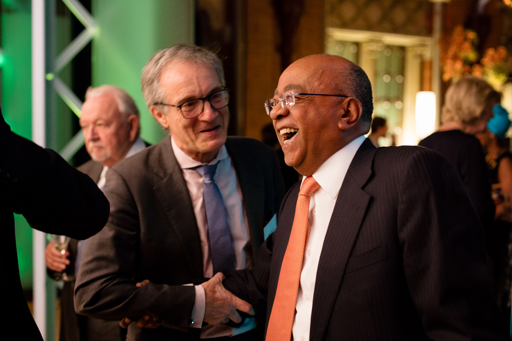 Businessmen in suit laughing and shaking hands with Mo Ibrahim at gala event in London