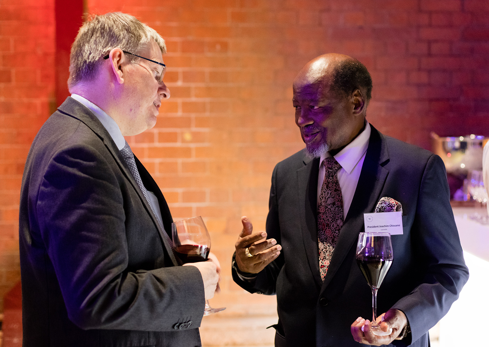 President Joaquim Chissano wearing grey suit making conversation with businessman at gala event in London