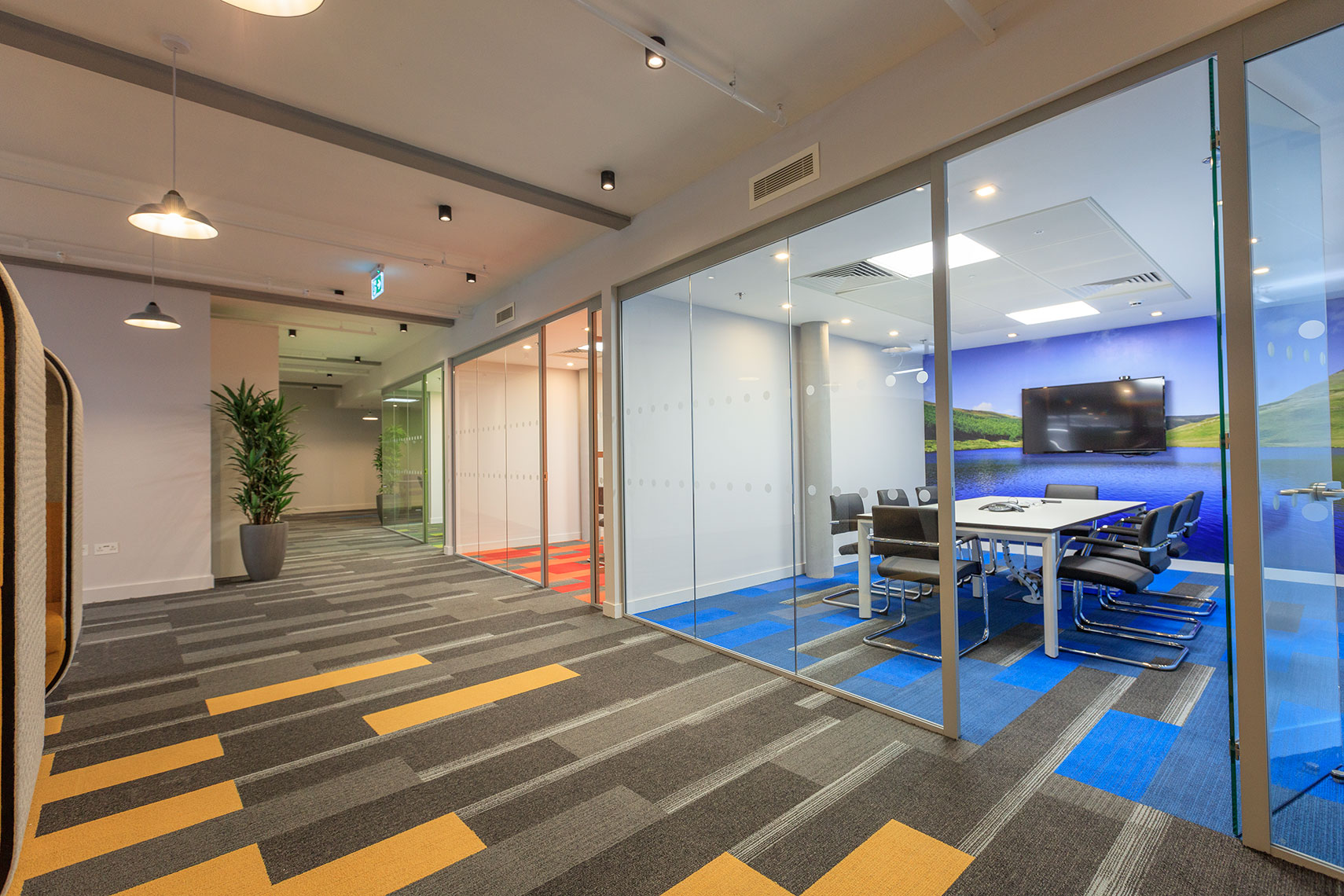 Interior fit-out of corporate office space with orange carpets and multicoloured offices in Manchester UK