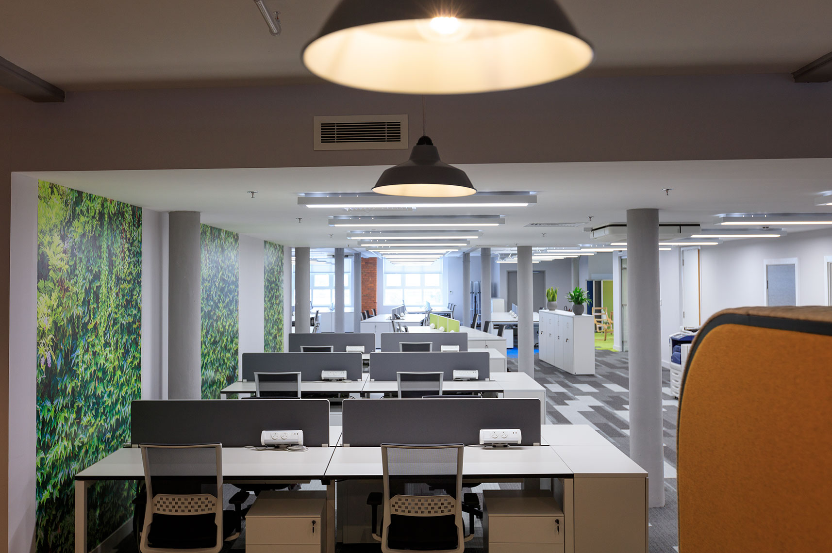 Corporate office spaces decorated with high-end multicoloured desks and natural lighting fixtures