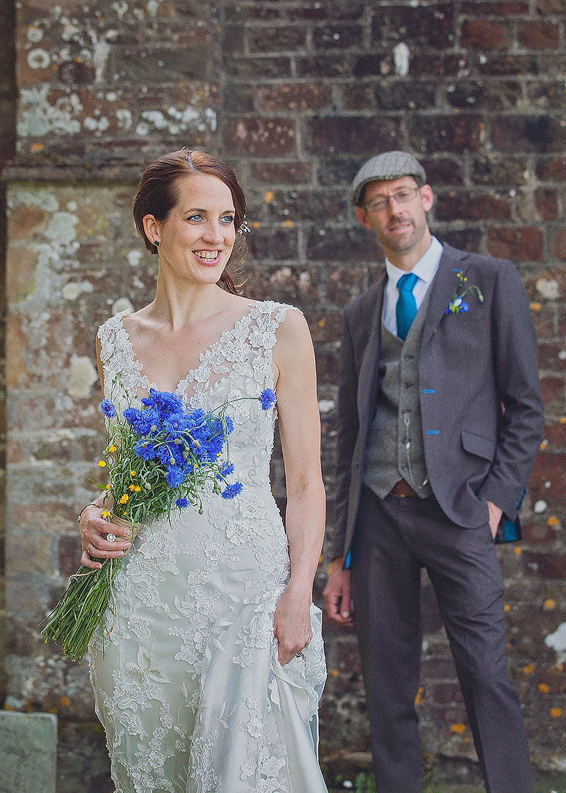 Beautiful smiling bride with white dress standing in front of smiling groom in grey vintage suit