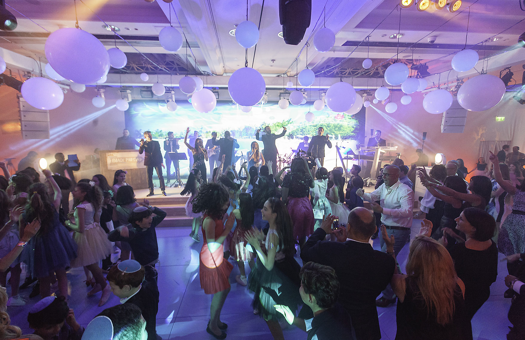 Bat mitzvah  taking place in large ballroom with dancing guests in London hotel