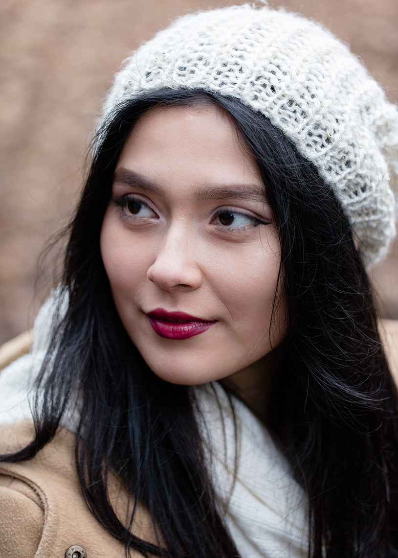 Beautiful young girl wearing white beret and red lipstick looking to the side