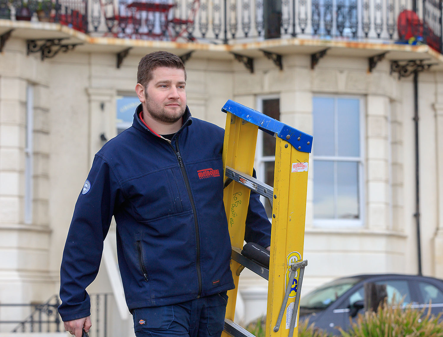 Young man with blue jacket carrying yellow ladder outside of building