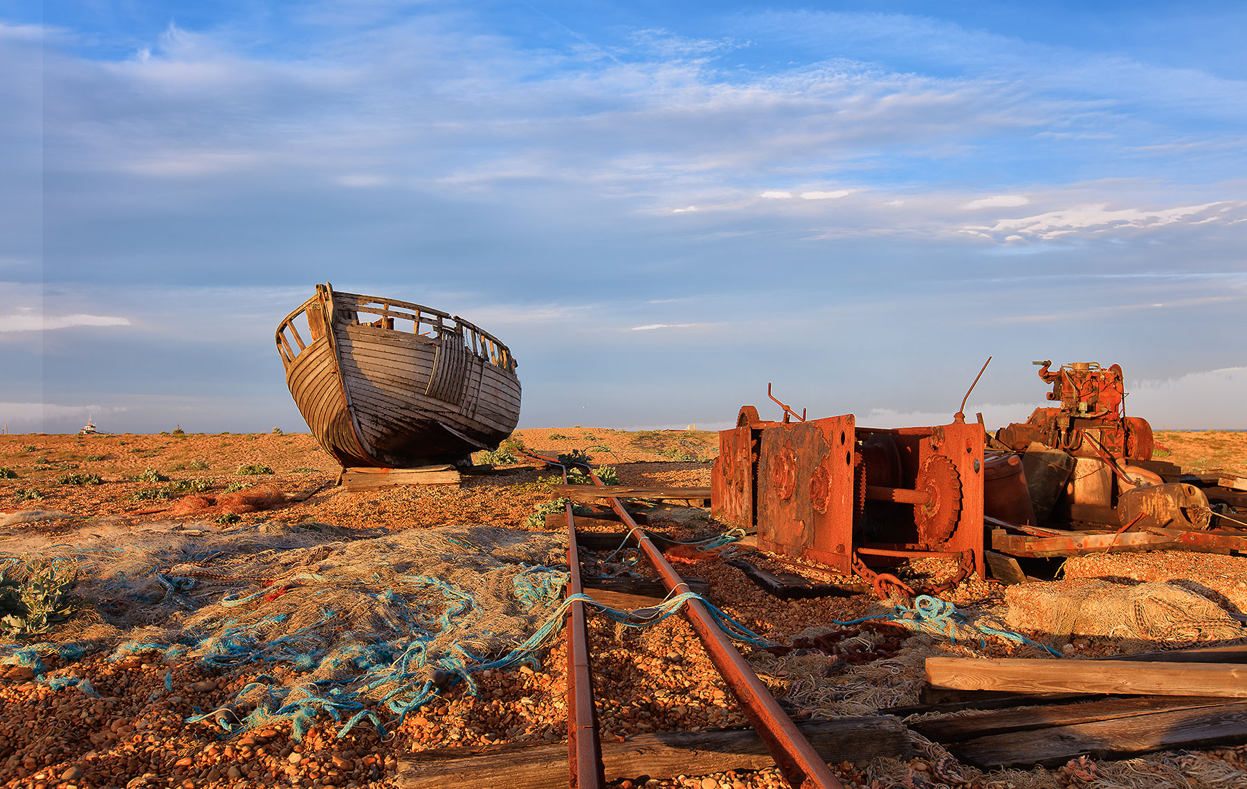 Fine-art landscape of old weathered boat and train tracks in Dungeoness, UK