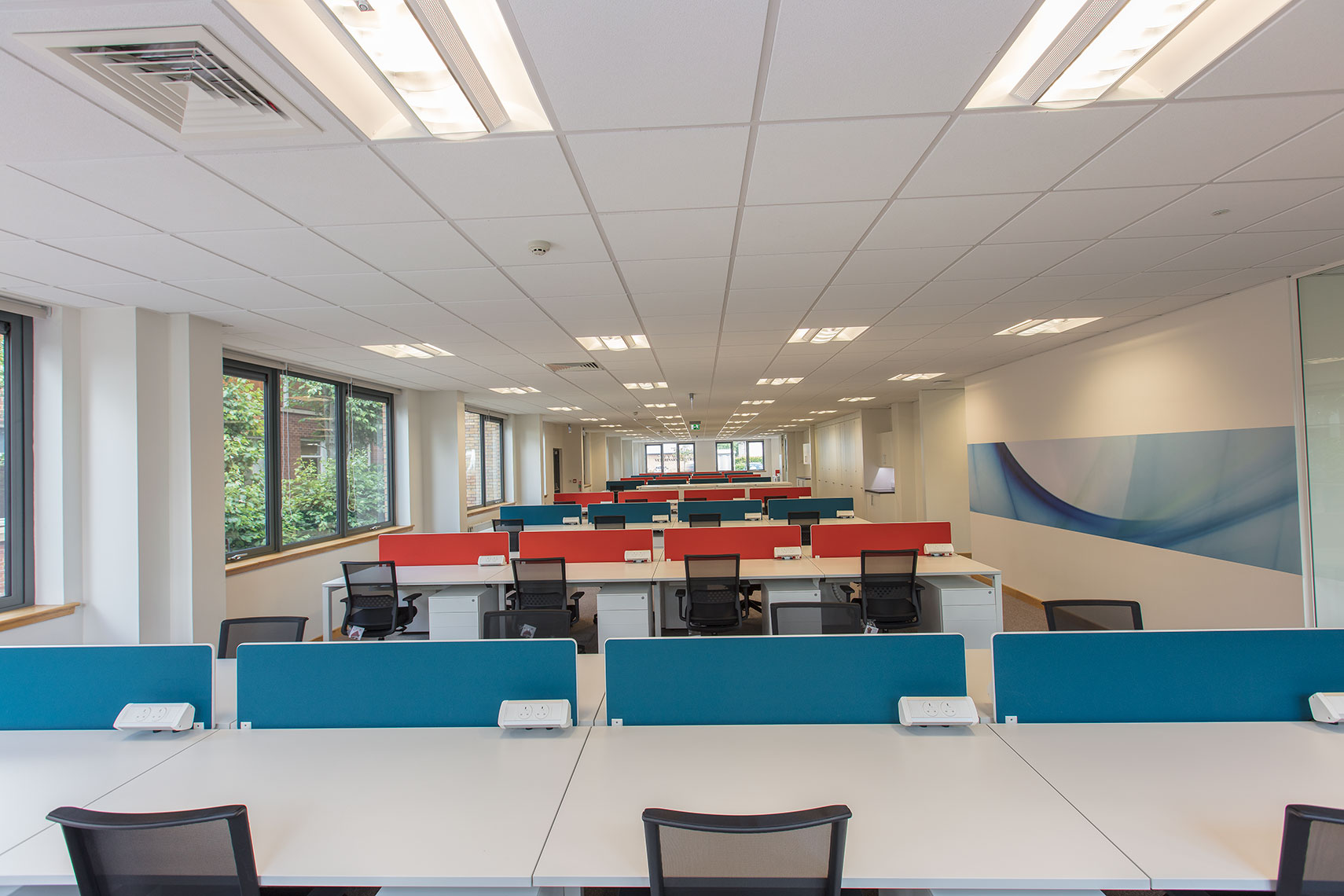 Office fit-out of Scotland corporate office space with multi-coloured tables and worktops