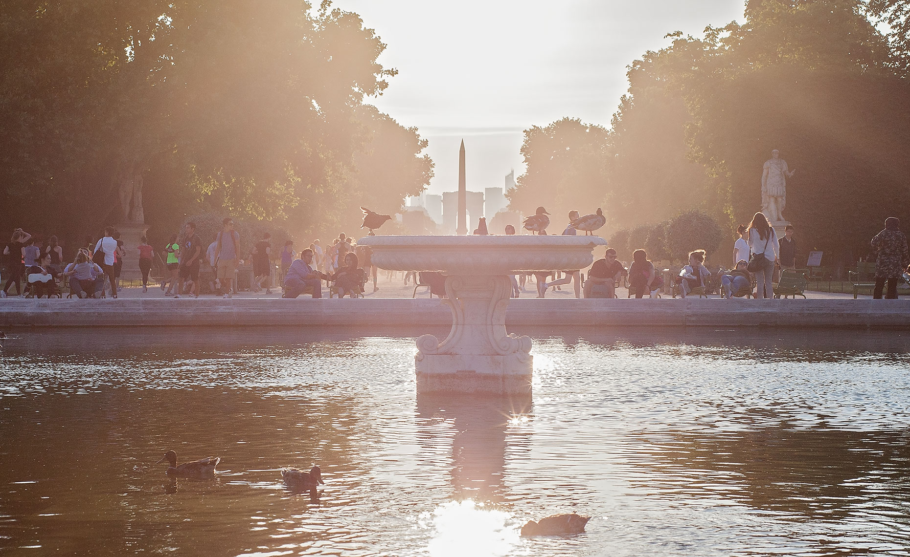 Sun setting over fountain and monuments in Paris, France