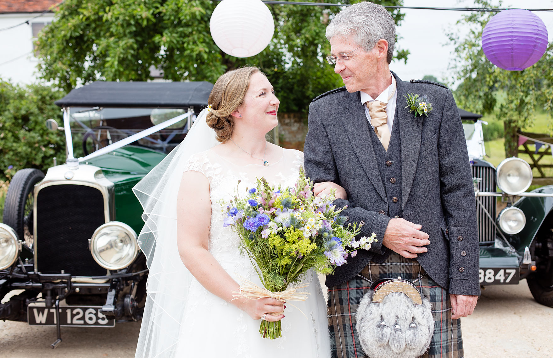 Happy smiling bride in white holding bouquet of flowers and making eye contact with farther in a kilt