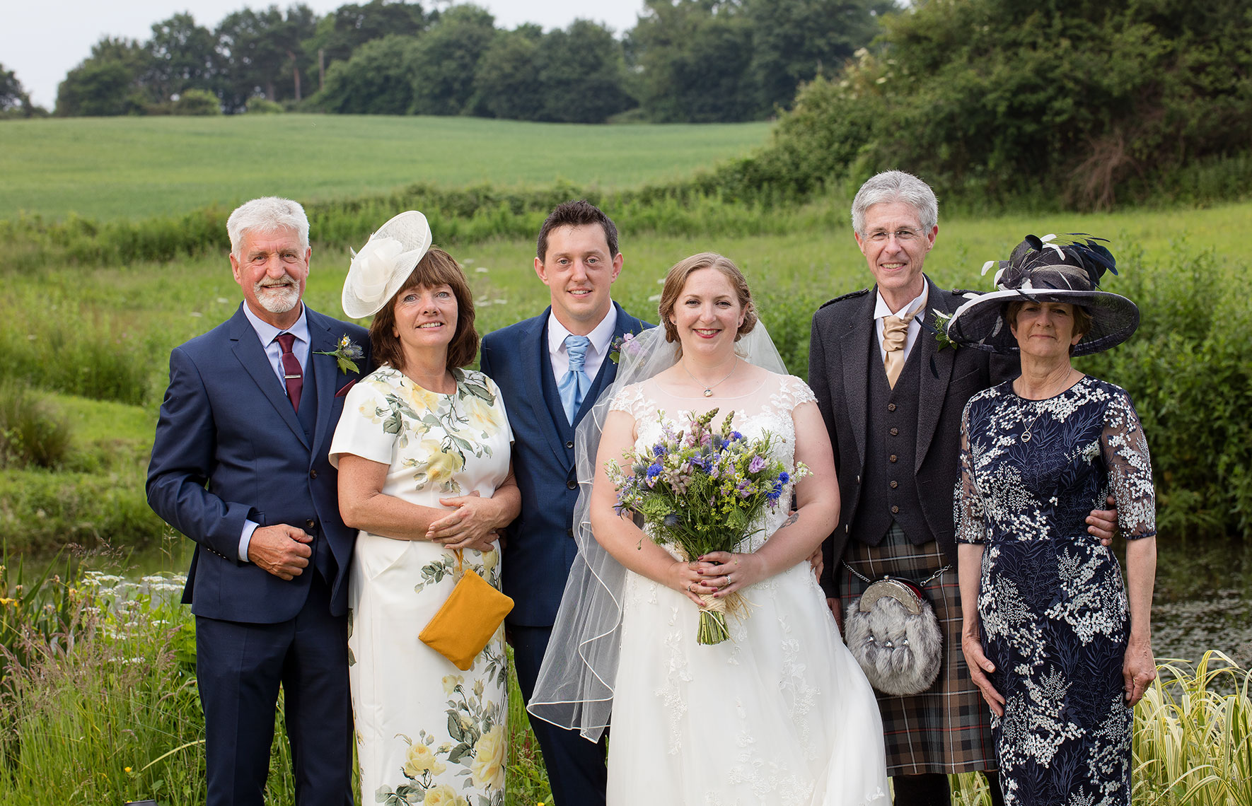 Handsome groom and smiling beautiful bride pose for group wedding photo with parents