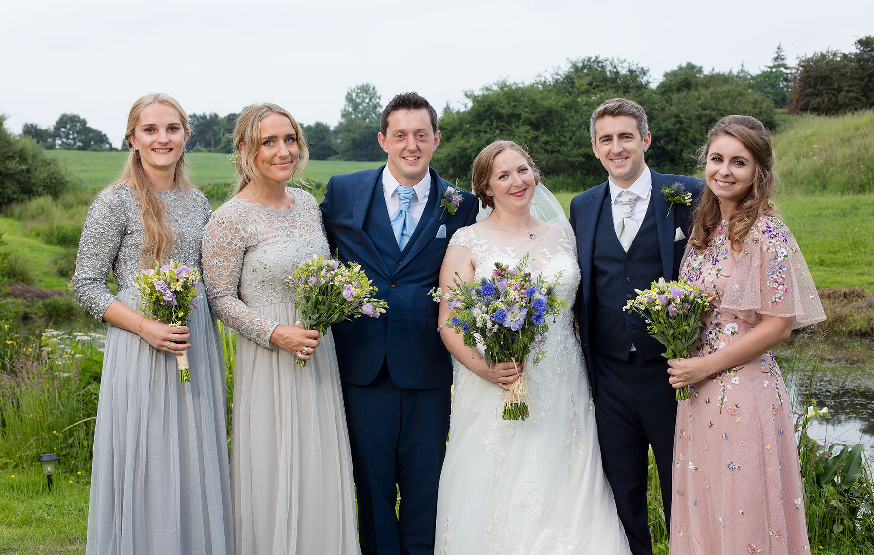 Bride Groom and Bridesmaids pose outdoors in countryside for wedding