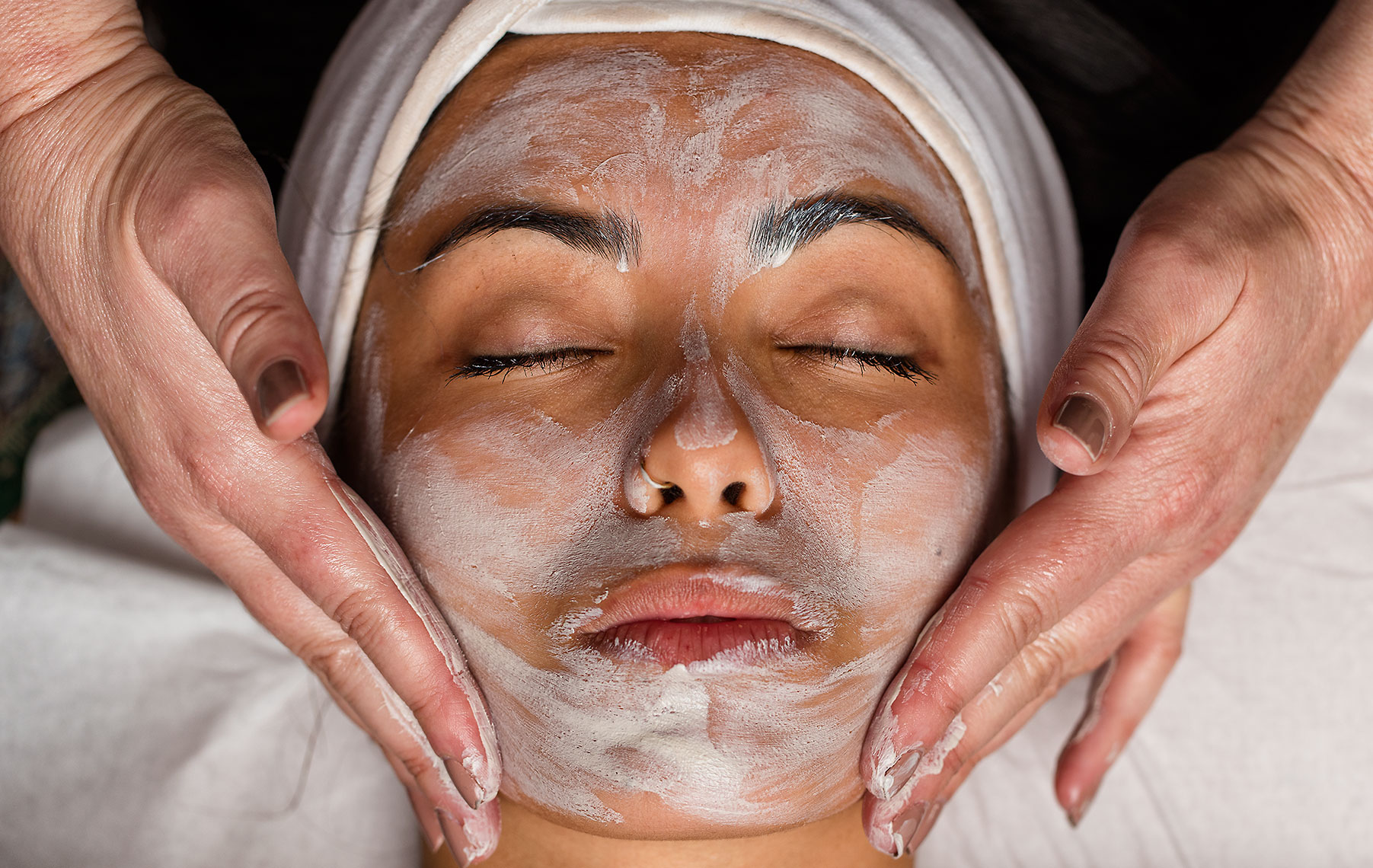 Hands of beauty therapist applying a facial mask to relaxed young lady