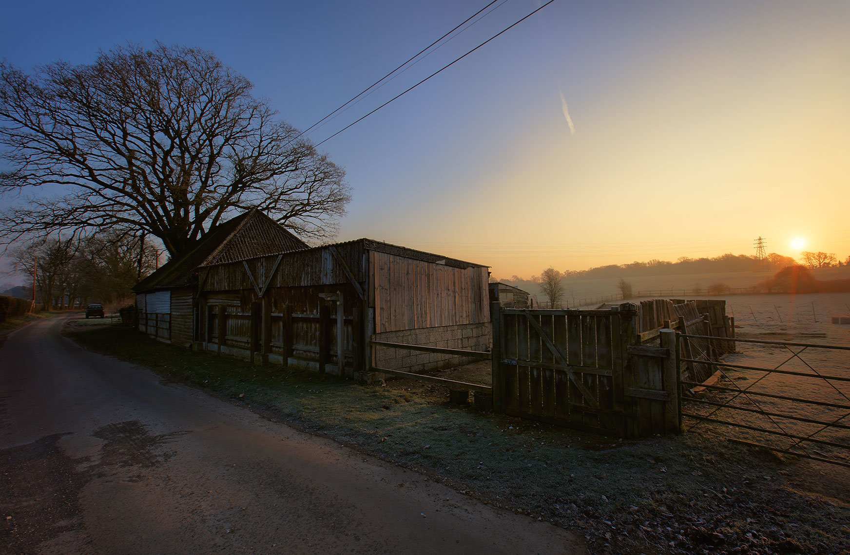 Sun rising over the hills of a countryside farm and barn in Hampshire, UK