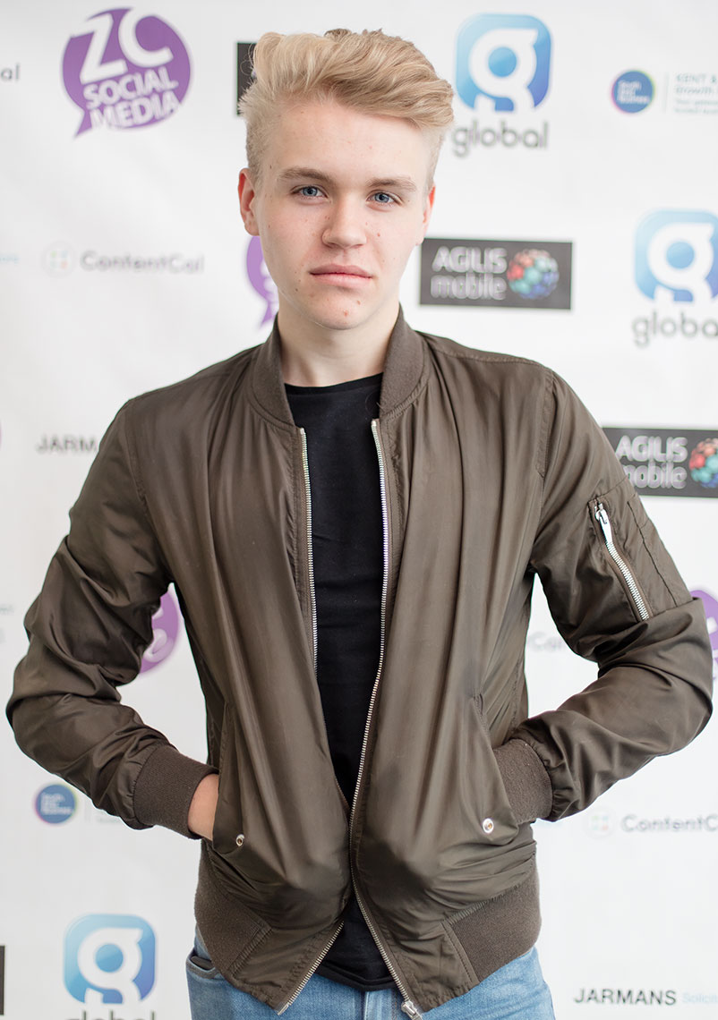 Handsome young man in leather jacket in front of corporate signage at business event
