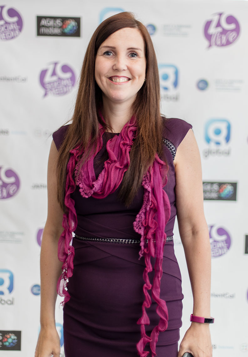Young lady fitted purple dress in front of corporate signage at business event