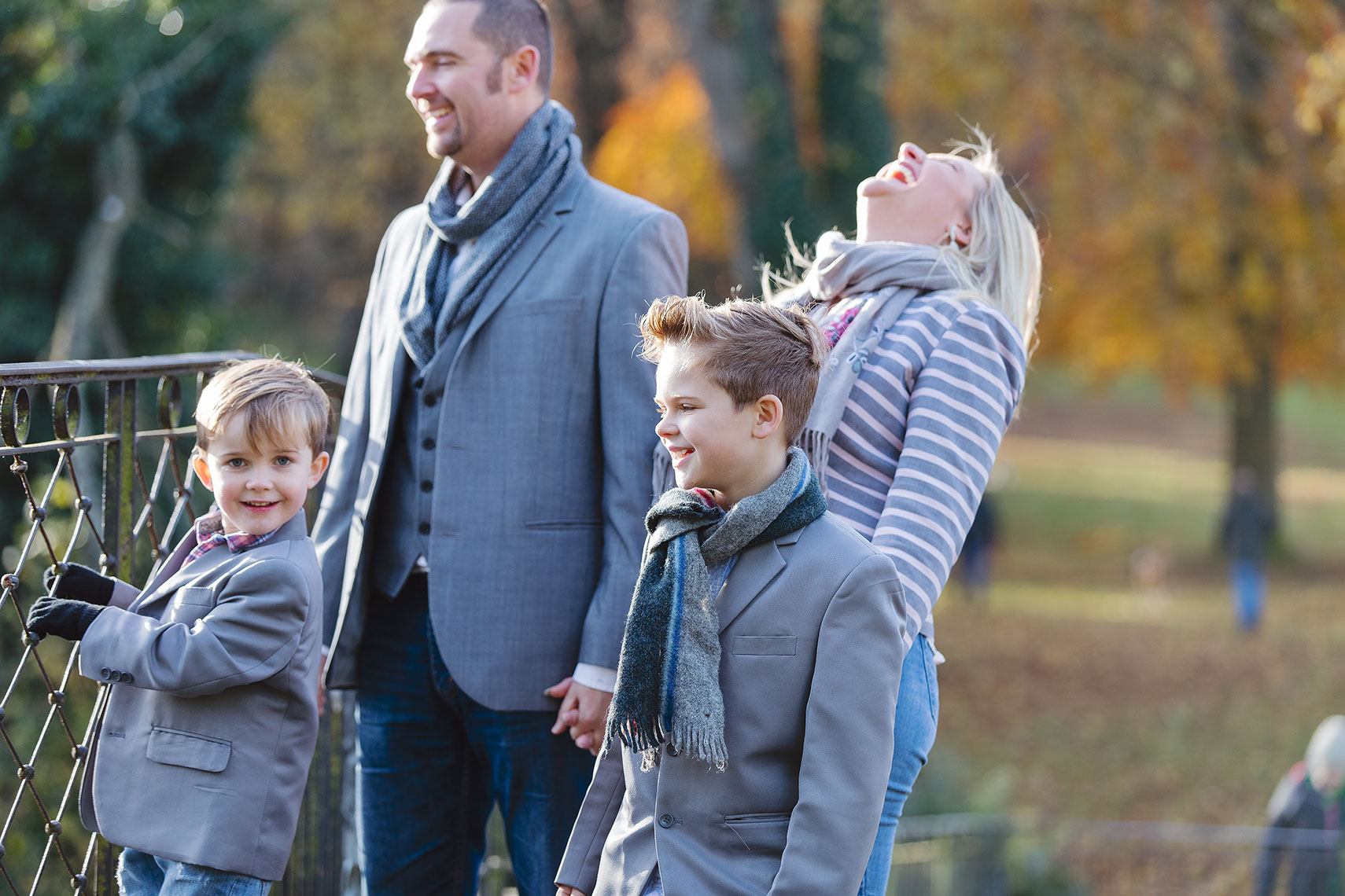 Young family with man in grey coat and blonde laughing woman holding hands of young boys wearing grey suits