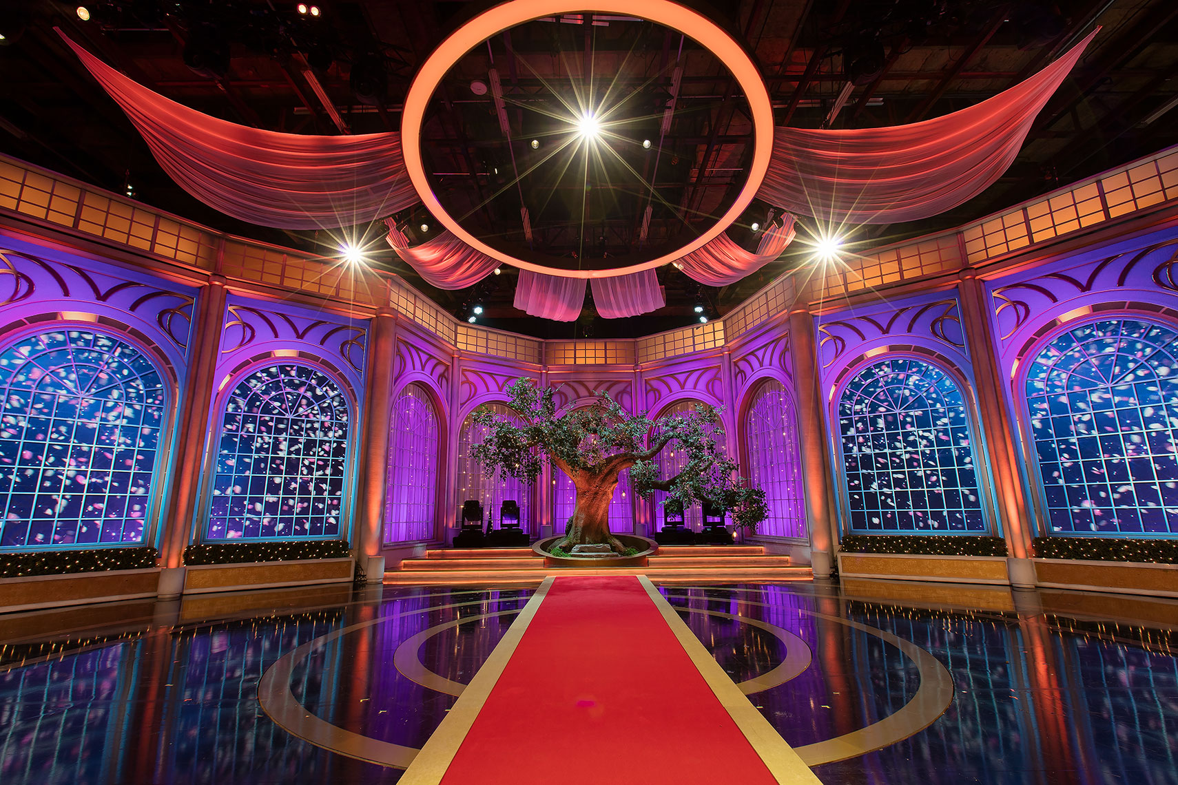 Interior television studio set with colourful banners, walls against a black glossy floor
