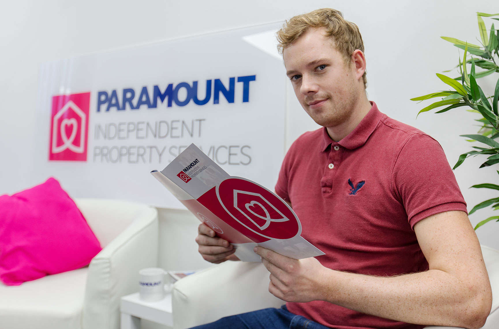 Smiling handsome young blond man reading corporate marketing brochures in business office