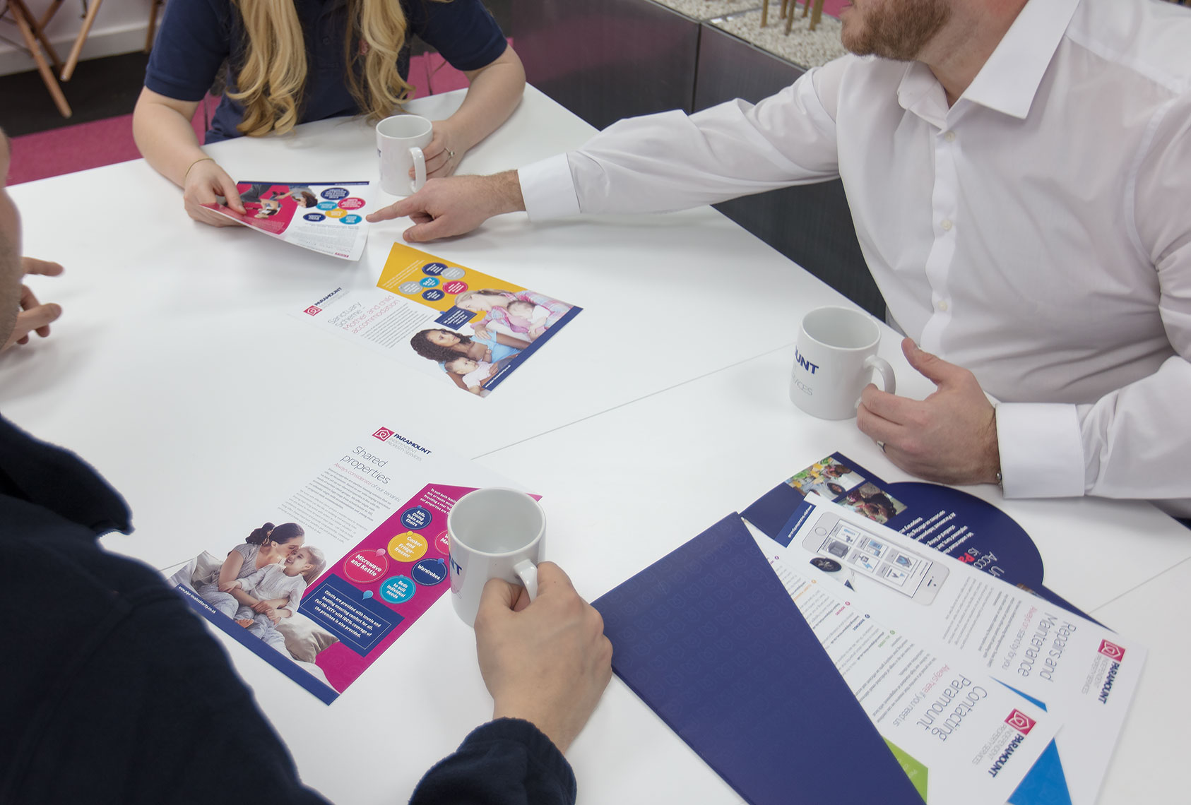 Office business team collaborating around a table covered in marketing material and brochures