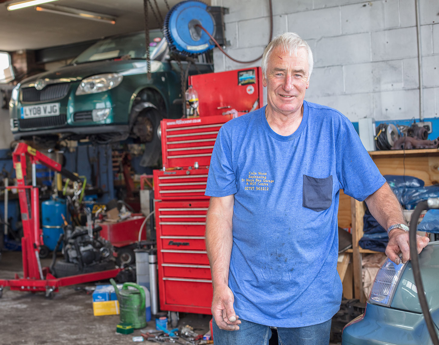Older male automotive engineer in blue shirt smiling and standing in front of garage