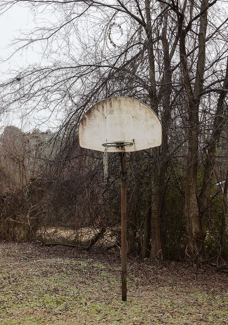 Tattered basketball hoop and net in old country backyard in Arkansas