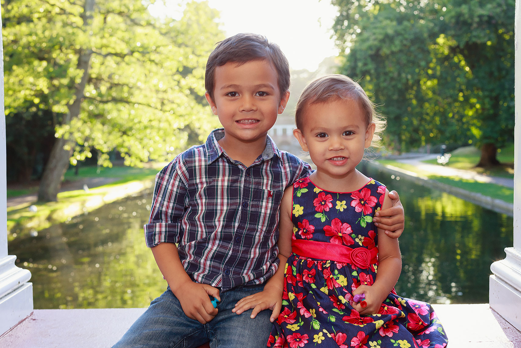 Adorable young boy in blue shirt holding younger sister in red dress sitting in front of small river
