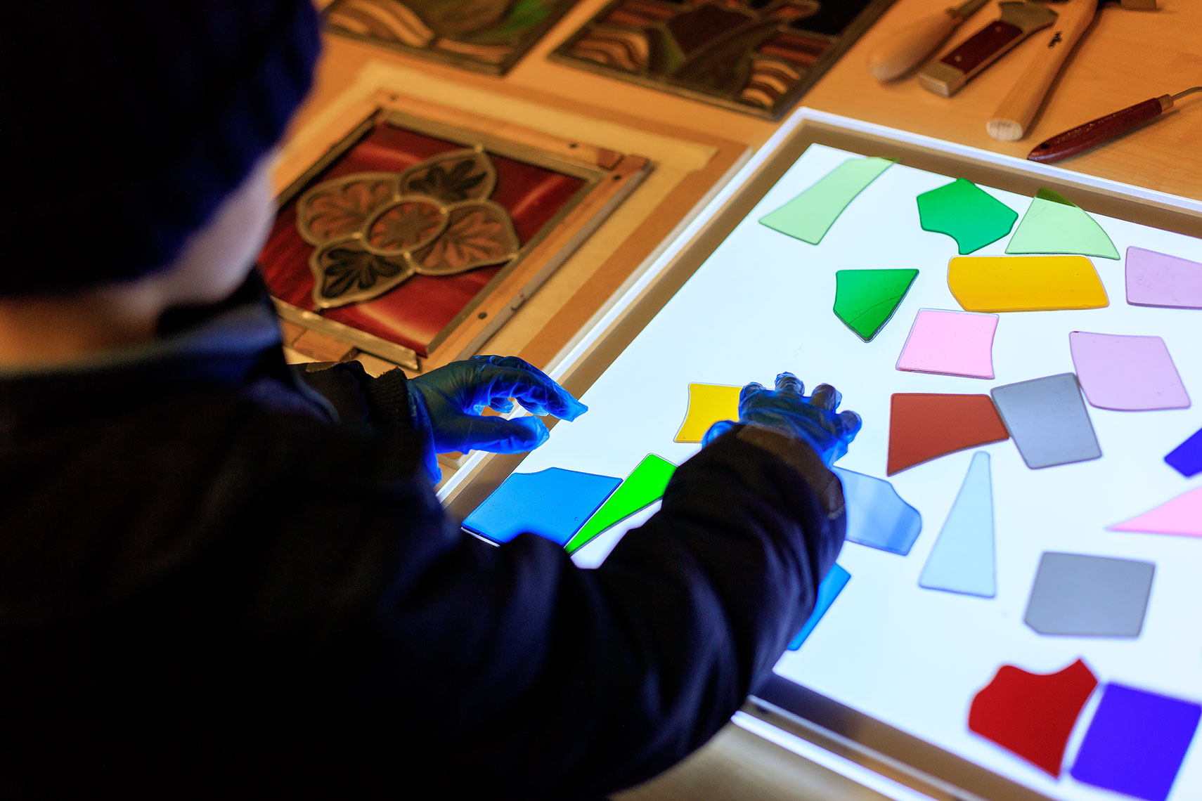 Young child with dark jacket and dark hat arranging multicoloured pieces of stained glass