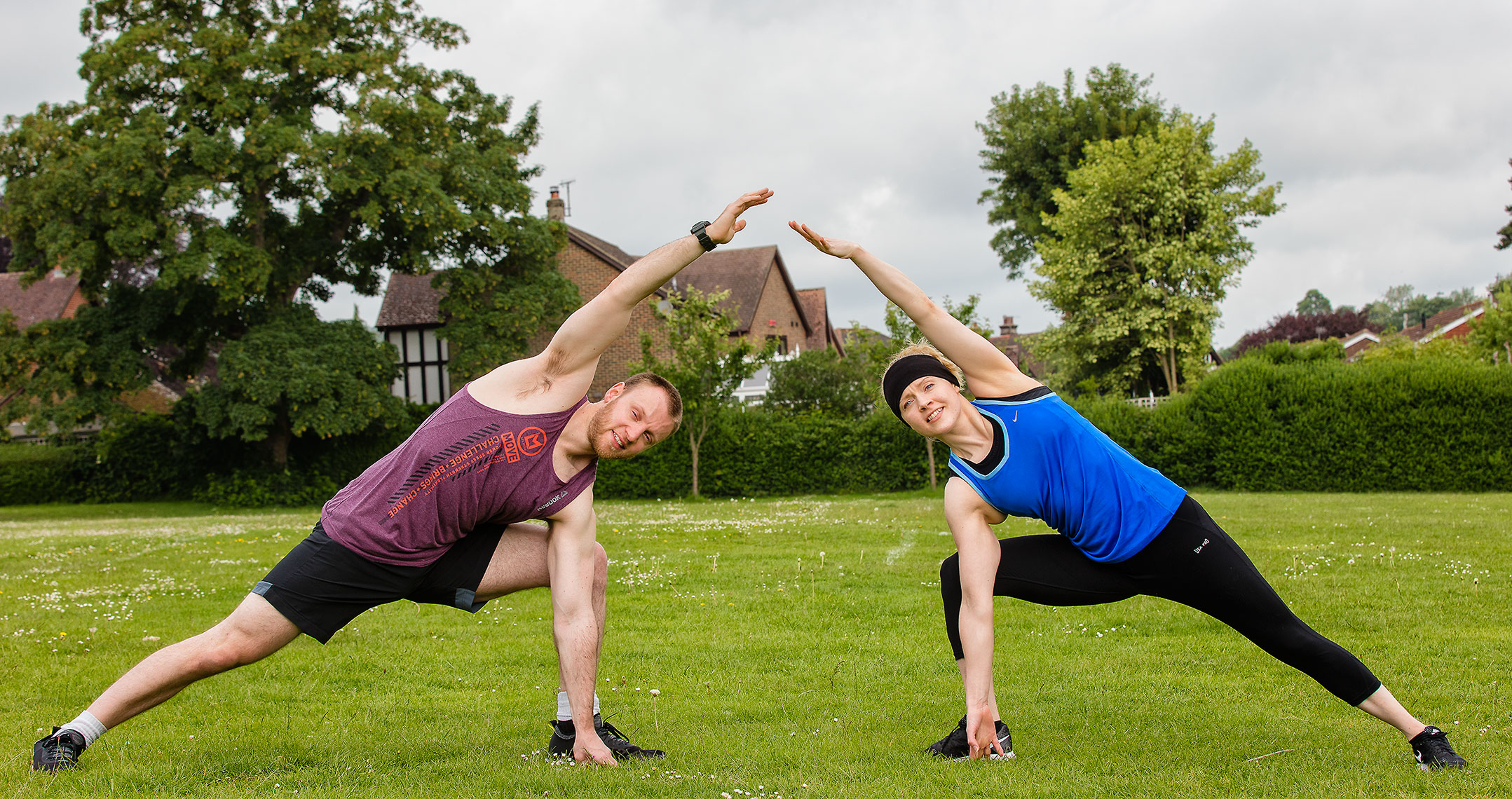 Young male and female fitness instructors outside stretching