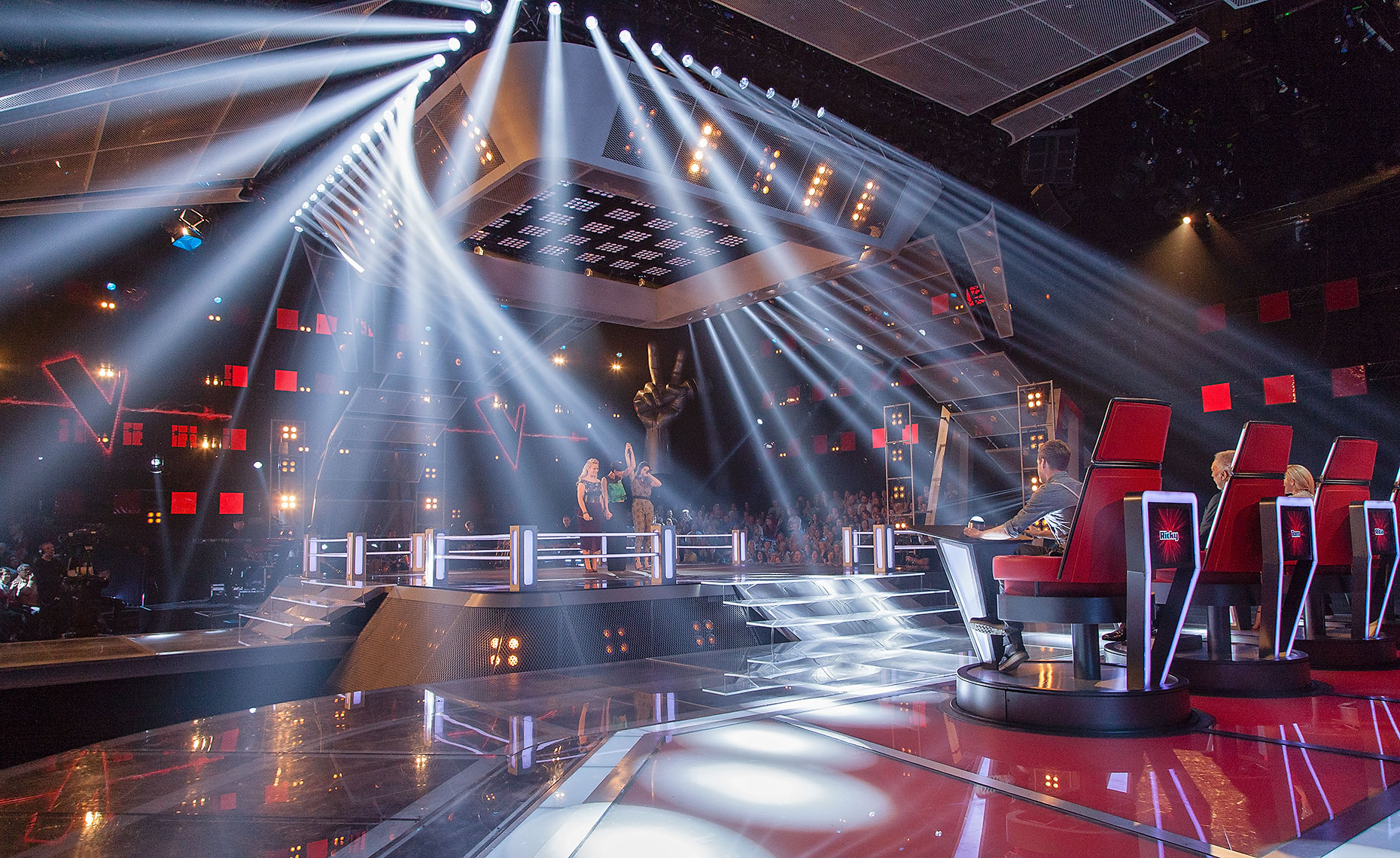 Interior television studio set The Voice with seated presenters and performer on stage