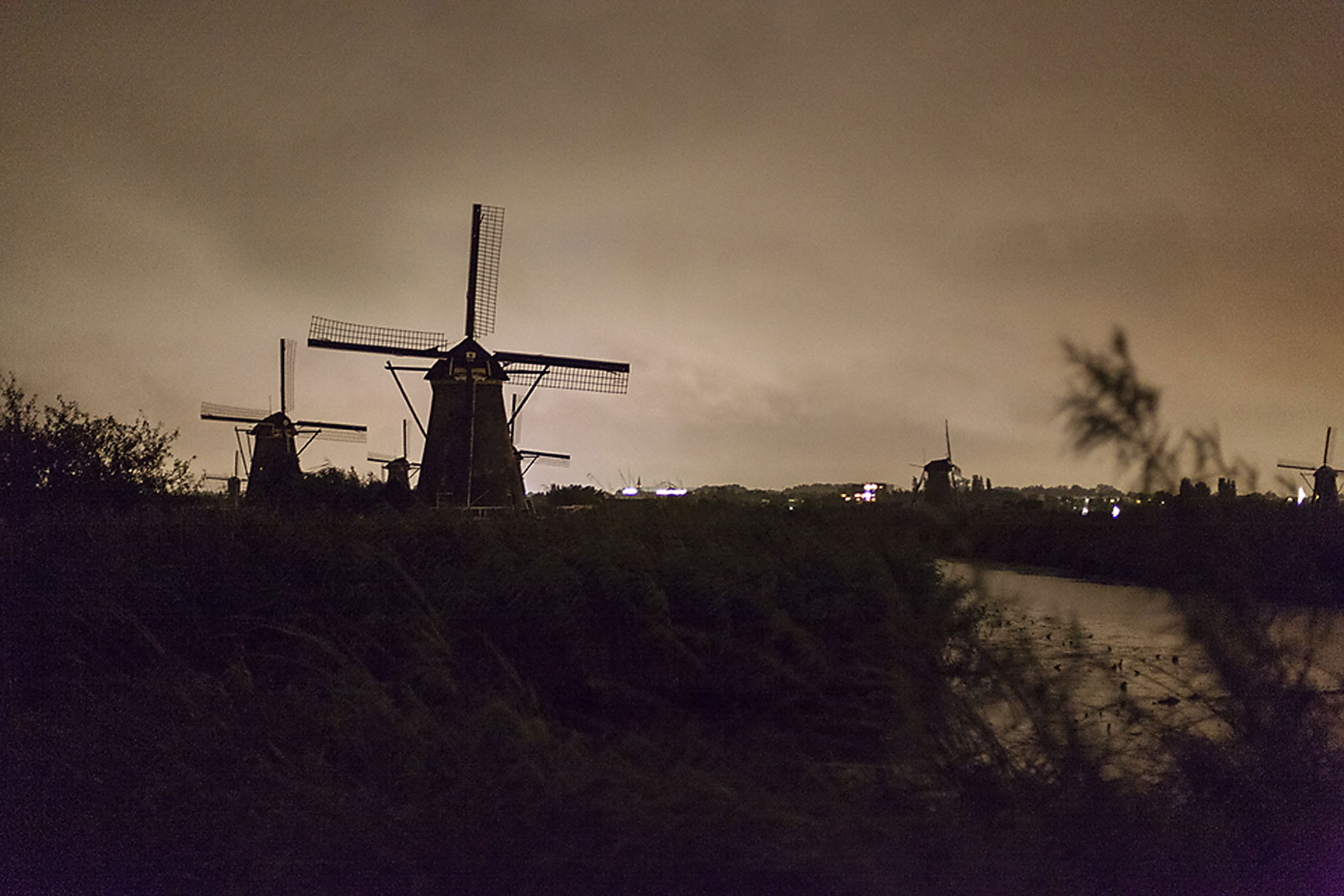 Windmills in Holland under the early dawn light next to small river and fields