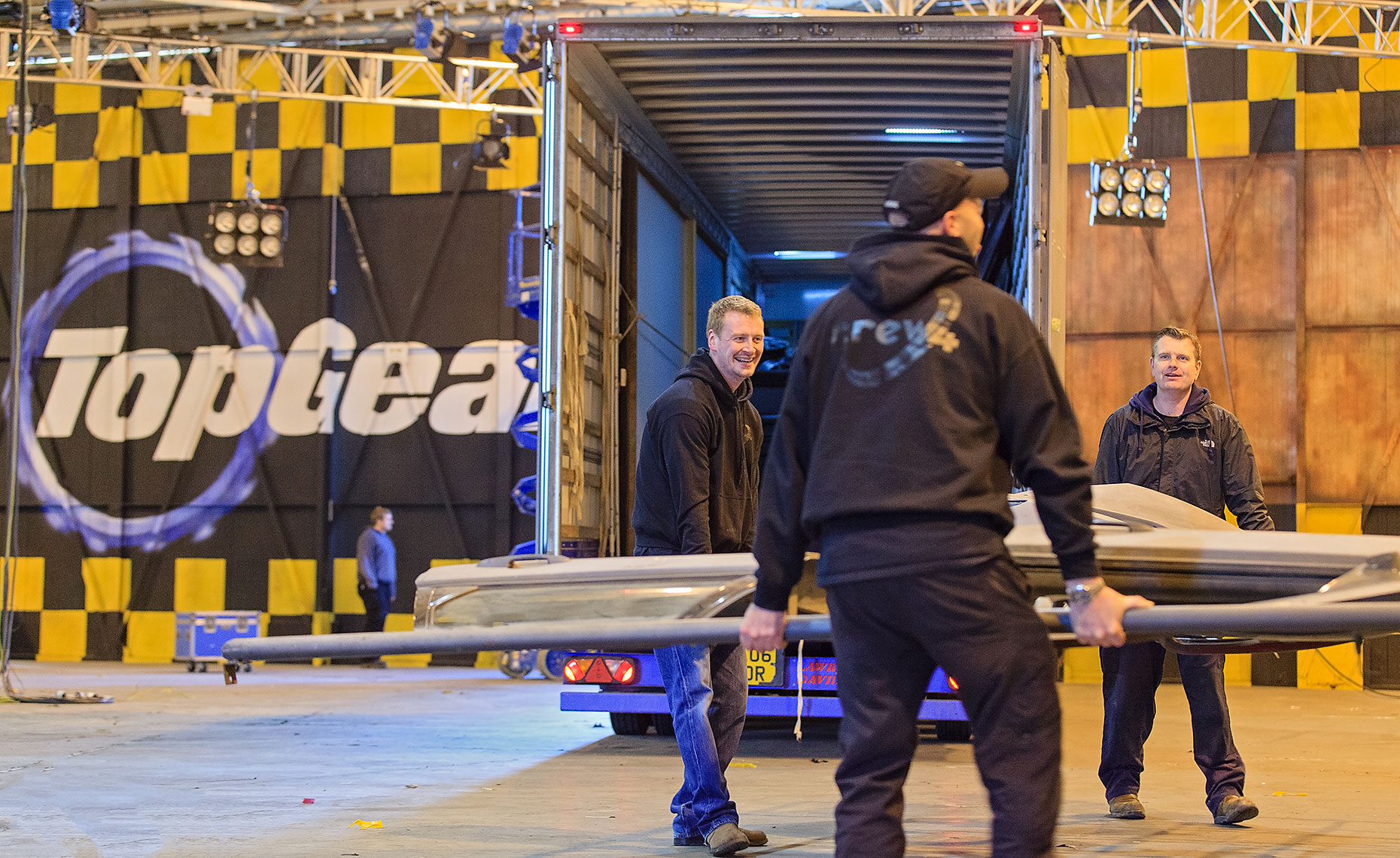 Production crew members carrying equipment onto BBC set for television show Top Gear