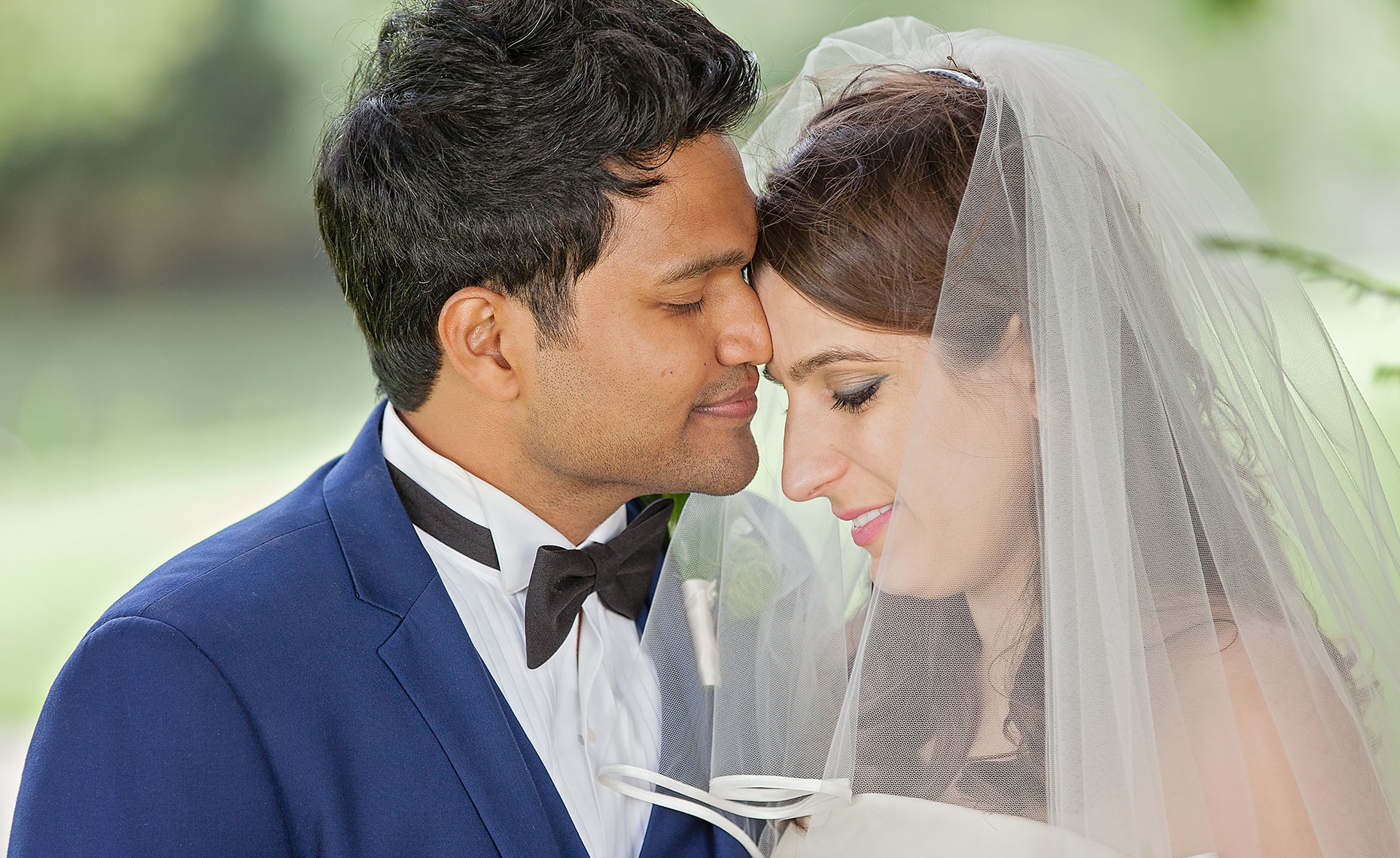 Handsome groom in blue suit with dark skin resting forehead on bride with white veil