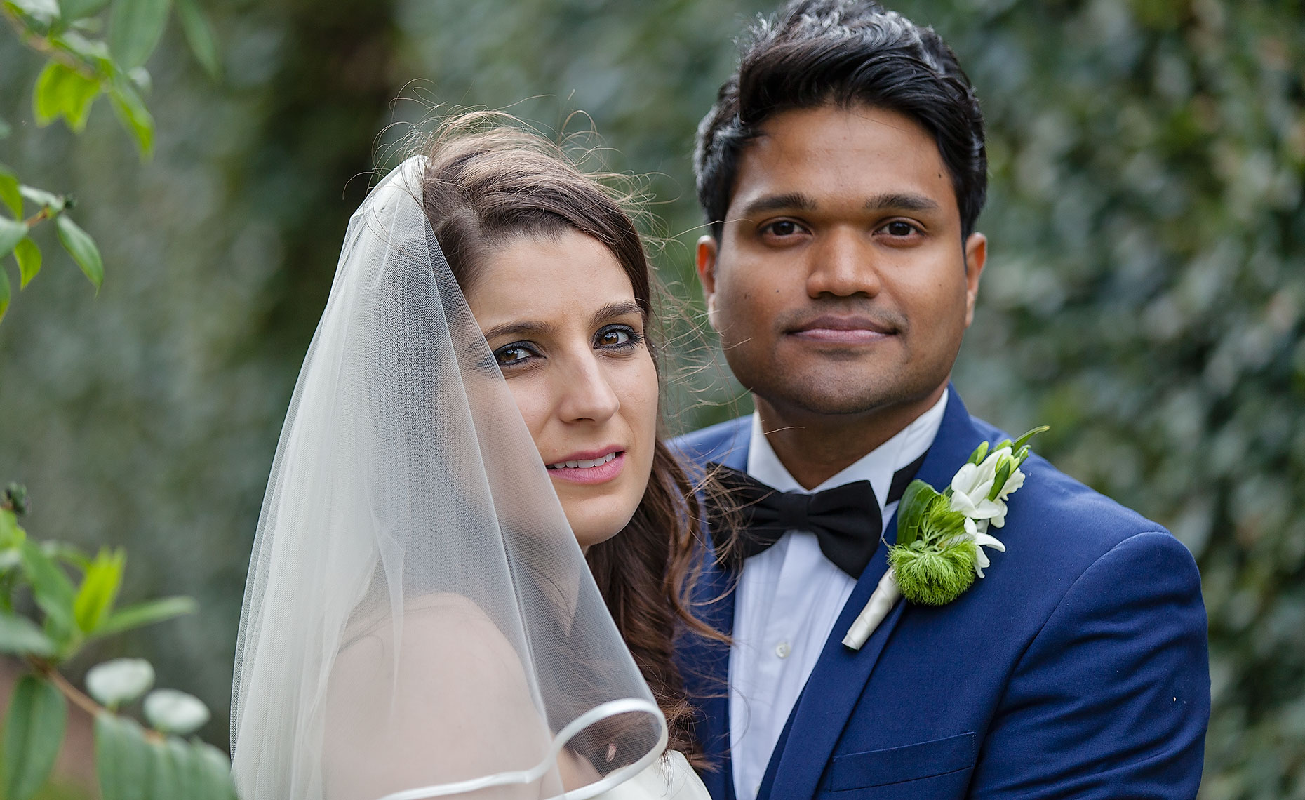 Groom with dark skin wearing blue suit standing next to beautiful bride with white veil in garden area