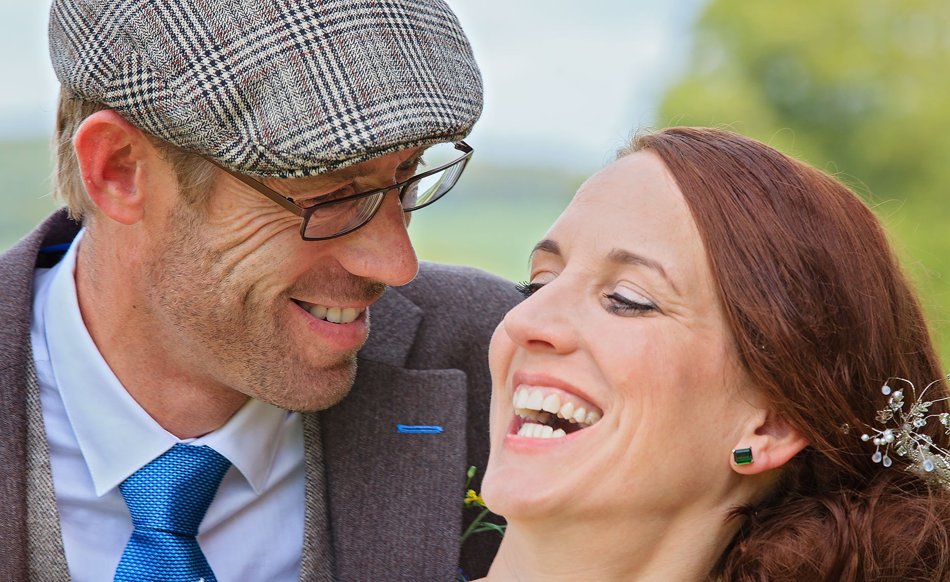 Groom with brown hat cradling smiling bride while laughing