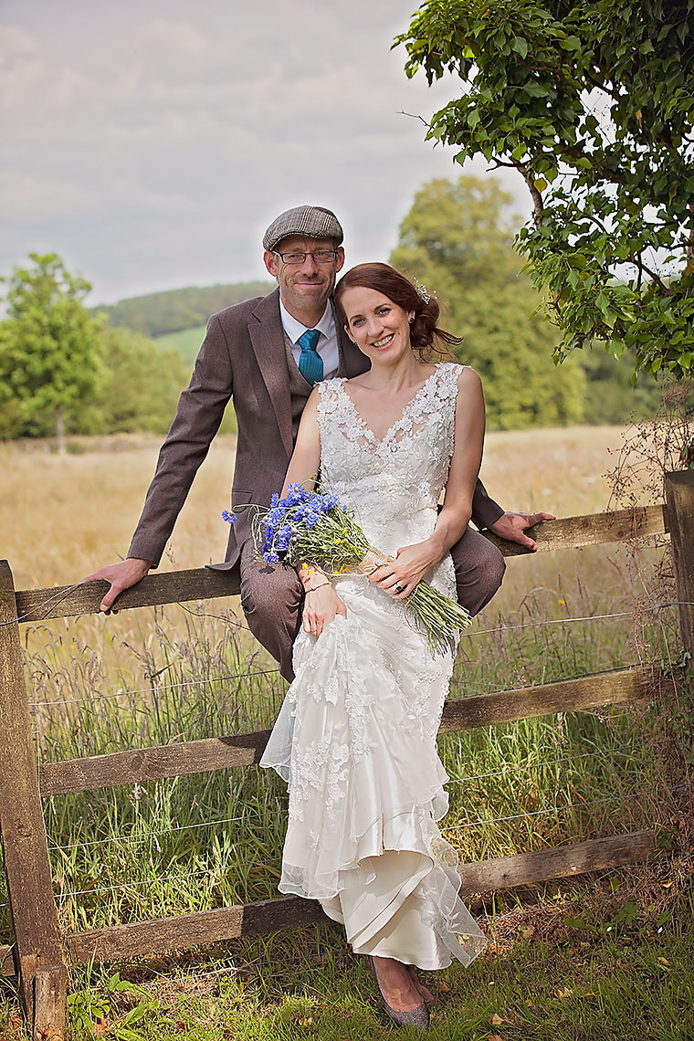 Smiling wedding couple with groom cradling bride against wooden fencing in front of countryside fields